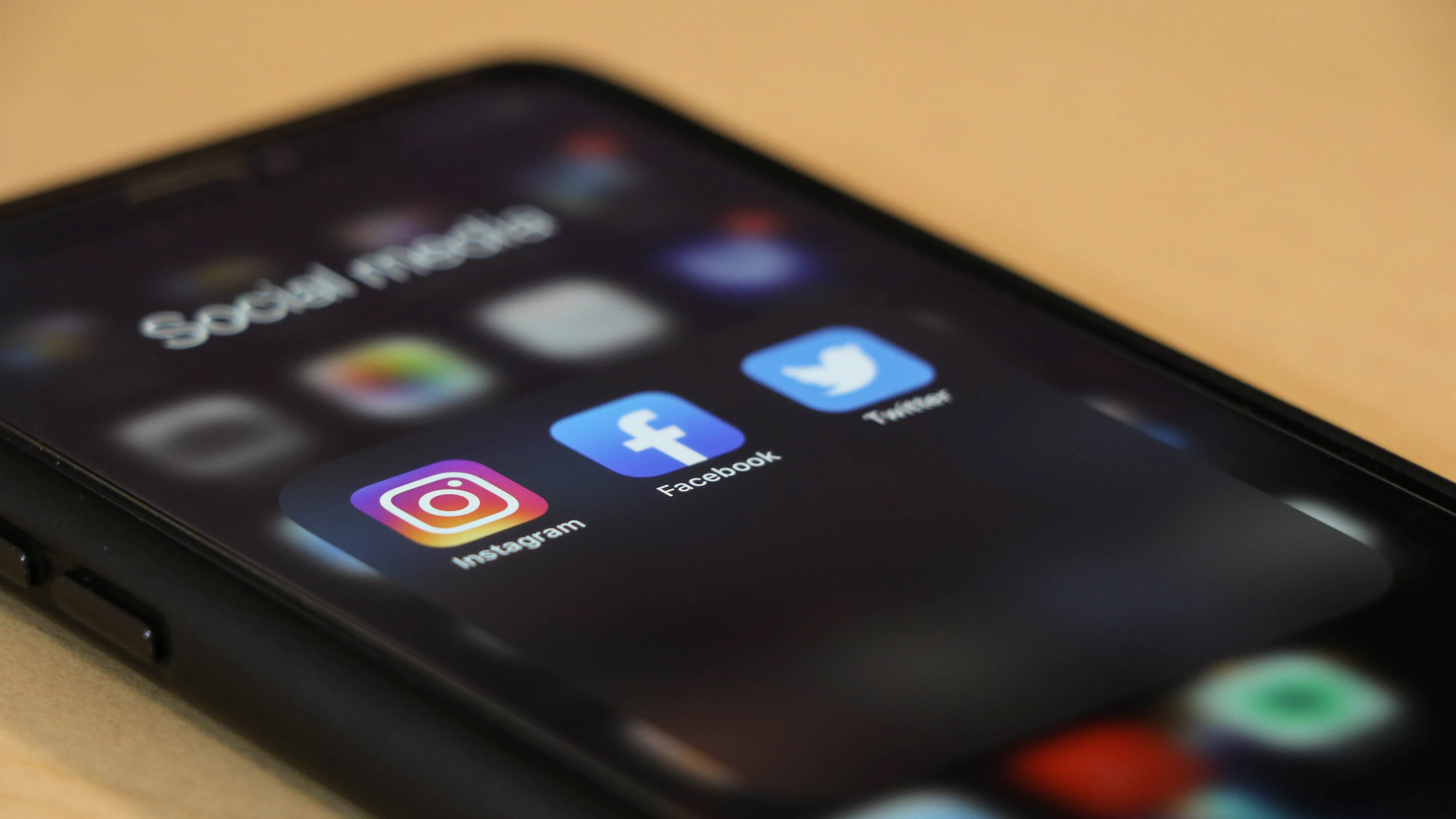 cell phone showing social media channels Instagram, Facebook and Twitter