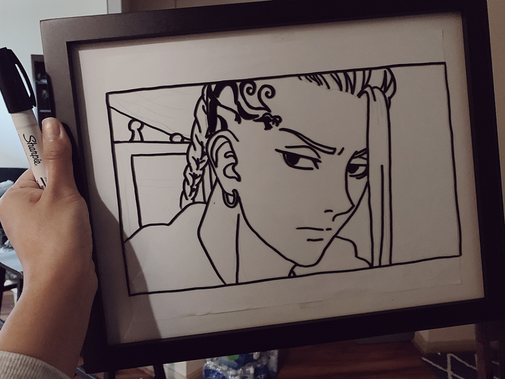 """A person holding up a glass in black picture frame with an outline of the anime character Draken from """"Tokyo Revengers."""""""