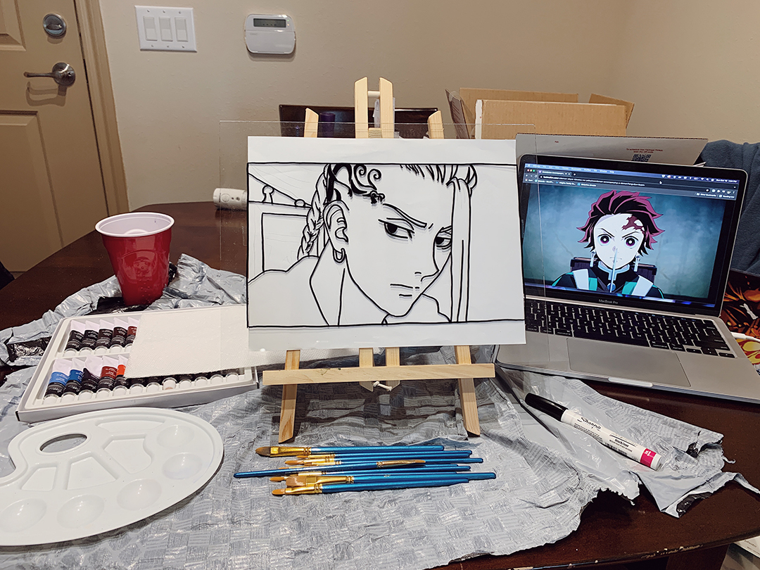 View of a wood dining table with a canvas holding glass art with paint brushes, color tubes and palette sitting beside it.